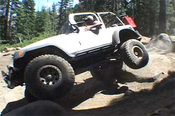 Jeep going over a big rock